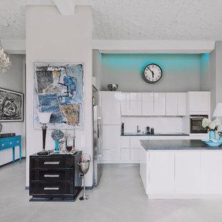 Offene, Mittelgroße Moderne Küche in L-Form mit flächenbündigen Schrankfronten, weißen Schränken, Küchenrückwand in Weiß, Betonboden, Kücheninsel, grauem Boden, grauer Arbeitsplatte und schwarzen Elektrogeräten in Berlin