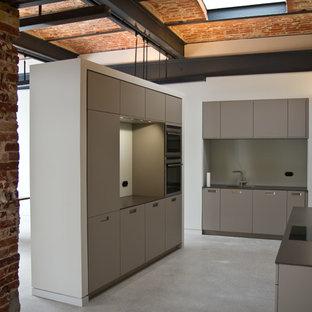 Ejemplo de cocina industrial, de tamaño medio, cerrada, sin isla, con armarios con paneles lisos, puertas de armario grises, salpicadero verde, fregadero de un seno y electrodomésticos con paneles