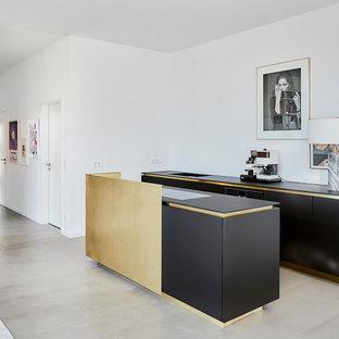 Offene, Zweizeilige, Mittelgroße Moderne Küche mit integriertem Waschbecken, schwarzen Schränken, schwarzen Elektrogeräten, Betonboden, Kücheninsel, grauem Boden, schwarzer Arbeitsplatte, flächenbündigen Schrankfronten und Küchenrückwand in Weiß in Köln