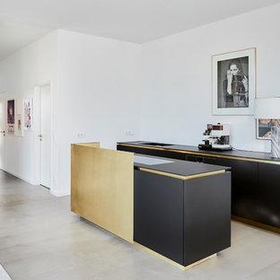 Offene, Zweizeilige, Kleine Moderne Küche mit flächenbündigen Schrankfronten, schwarzen Schränken, Kücheninsel, grauem Boden, schwarzer Arbeitsplatte und Küchenrückwand in Weiß in Köln