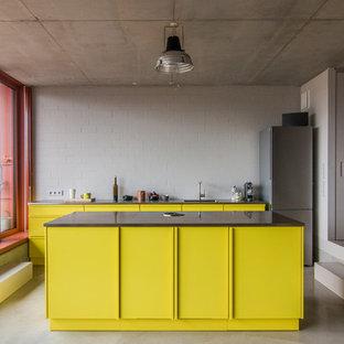 Inspiration för mellanstora industriella kök, med en enkel diskho, släta luckor, gula skåp, rostfria vitvaror, betonggolv, en köksö och grått stänkskydd