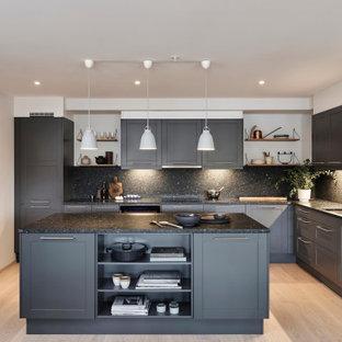 Große Klassische Küche in L-Form mit Unterbauwaschbecken, Schrankfronten im Shaker-Stil, grauen Schränken, Granit-Arbeitsplatte, Küchenrückwand in Grau, Küchengeräten aus Edelstahl, hellem Holzboden, Kücheninsel, beigem Boden und grauer Arbeitsplatte in Berlin