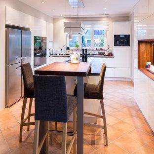 ハンブルクの巨大なモダンスタイルのおしゃれなキッチン (ドロップインシンク、フラットパネル扉のキャビネット、白いキャビネット、人工大理石カウンター、白いキッチンパネル、黒い調理設備、テラコッタタイルの床、赤い床、黒いキッチンカウンター) の写真