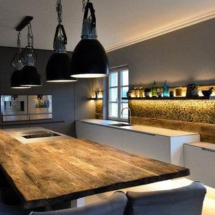 Mittelgroße Industrial Küche in L-Form mit integriertem Waschbecken, flächenbündigen Schrankfronten, weißen Schränken, Küchengeräten aus Edelstahl, Keramikboden, Halbinsel und weißem Boden in Köln