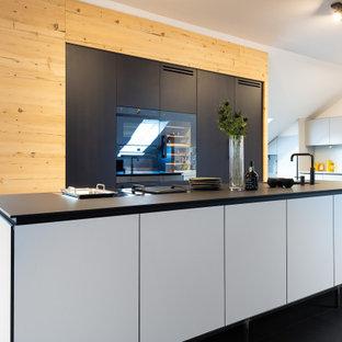 Mittelgroße Moderne Küche mit Unterbauwaschbecken, flächenbündigen Schrankfronten, schwarzen Schränken, schwarzen Elektrogeräten, Kücheninsel, schwarzem Boden und schwarzer Arbeitsplatte in München