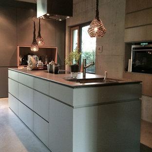 Große Moderne Küche mit flächenbündigen Schrankfronten, grauen Schränken, Kücheninsel, Unterbauwaschbecken, schwarzen Elektrogeräten und Betonboden in München