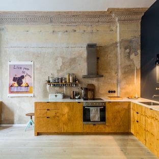 Geschlossene, Mittelgroße Industrial Küche ohne Insel in L-Form mit flächenbündigen Schrankfronten, hellbraunen Holzschränken, hellem Holzboden, beigem Boden, weißer Arbeitsplatte, Unterbauwaschbecken, Küchenrückwand in Beige und Elektrogeräten mit Frontblende in Berlin
