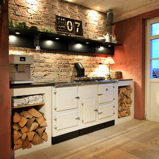 Design ideas for a mid-sized country l-shaped open plan kitchen in Dusseldorf with a farmhouse sink, raised-panel cabinets, light wood cabinets, limestone benchtops, black appliances, limestone floors, with island and beige floor.