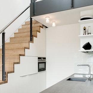 ハンブルクの小さいインダストリアルスタイルのおしゃれなキッチン (フラットパネル扉のキャビネット、白いキャビネット、コンクリートカウンター、白いキッチンパネル、ガラス板のキッチンパネル、一体型シンク、黒い調理設備) の写真