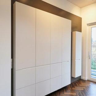 Idéer för stora funkis vitt kök med öppen planlösning, med en undermonterad diskho, släta luckor, bruna skåp, svarta vitvaror, mellanmörkt trägolv, en köksö och brunt golv