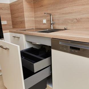 ミュンヘンの巨大なトラディショナルスタイルのおしゃれなL型キッチン (ダブルシンク、白いキャビネット、木材カウンター、ベージュキッチンパネル、木材のキッチンパネル、シルバーの調理設備の、ベージュのキッチンカウンター) の写真