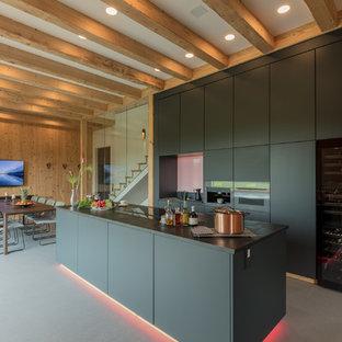 Zweizeilige, Offene, Große Moderne Küche mit flächenbündigen Schrankfronten, schwarzen Schränken, Kücheninsel, grauem Boden, schwarzer Arbeitsplatte und schwarzen Elektrogeräten in Stuttgart