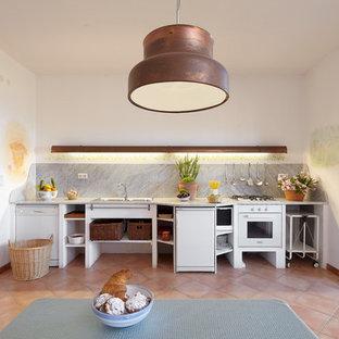 Foto di una grande cucina mediterranea con nessun'anta, ante bianche, paraspruzzi grigio, elettrodomestici bianchi, pavimento in terracotta, nessuna isola e pavimento arancione