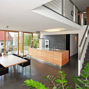 Diseño de cocina comedor actual, de tamaño medio, con fregadero integrado, armarios con paneles lisos, puertas de armario negras, encimera de acero inoxidable, electrodomésticos de acero inoxidable, suelo de cemento y una isla