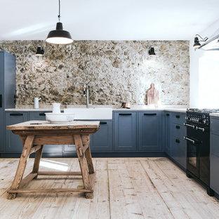 Geräumige Urige Küche in L-Form mit Landhausspüle, Schrankfronten im Shaker-Stil, blauen Schränken, schwarzen Elektrogeräten, hellem Holzboden, Kücheninsel, beigem Boden und beiger Arbeitsplatte in München