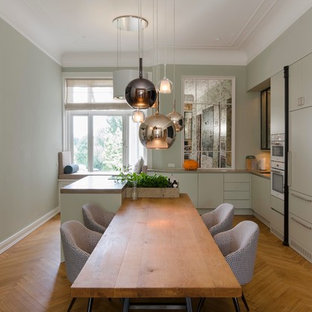 Photo of a large scandinavian kitchen in Hamburg with green cabinets, limestone benchtops, medium hardwood floors and with island.