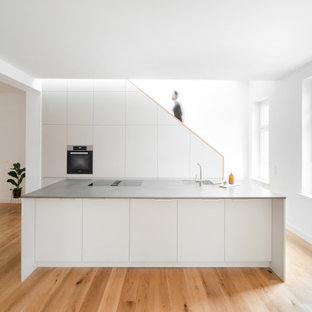 Offene, Große, Zweizeilige Moderne Küche mit flächenbündigen Schrankfronten, weißen Schränken, Arbeitsplatte aus Holz, Kücheninsel, integriertem Waschbecken, Elektrogeräten mit Frontblende, braunem Holzboden, braunem Boden und grauer Arbeitsplatte in Berlin