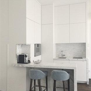 Modelo de cocina en L, minimalista, pequeña, abierta, con fregadero encastrado, armarios con paneles lisos, puertas de armario blancas, encimera de mármol, salpicadero multicolor, salpicadero de losas de piedra, electrodomésticos negros, suelo de madera oscura y encimeras grises