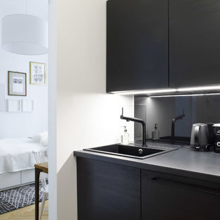 This is an example of a small modern single-wall separate kitchen in Berlin with an integrated sink, louvered cabinets, black cabinets, laminate benchtops, black splashback, metal splashback, black appliances, medium hardwood floors, no island and brown floor.