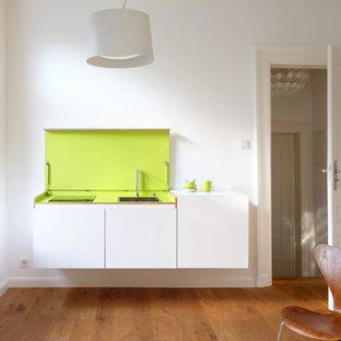 Kleine, Offene, Einzeilige Moderne Küche mit Waschbecken, flächenbündigen Schrankfronten, weißen Schränken, braunem Holzboden und Kücheninsel in Düsseldorf