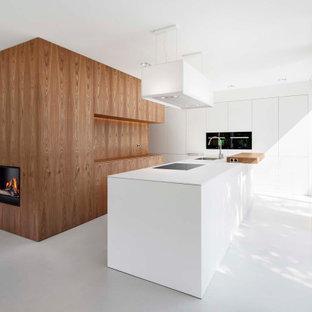Große Moderne Küche in L-Form mit Unterbauwaschbecken, flächenbündigen Schrankfronten, weißen Schränken, Mineralwerkstoff-Arbeitsplatte, Elektrogeräten mit Frontblende, Porzellan-Bodenfliesen, Kücheninsel, grauem Boden und weißer Arbeitsplatte in Düsseldorf