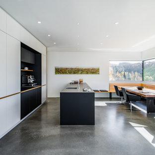 Zweizeilige Moderne Küche mit integriertem Waschbecken, flächenbündigen Schrankfronten, weißen Schränken, Betonboden, Kücheninsel und grauem Boden in München