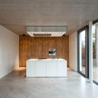 Offene, Zweizeilige, Mittelgroße Moderne Küche mit Einbauwaschbecken, flächenbündigen Schrankfronten, Küchengeräten aus Edelstahl, Betonboden, Kücheninsel, grauem Boden, weißer Arbeitsplatte und hellbraunen Holzschränken in Hamburg
