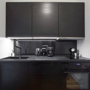 Modelo de cocina lineal, minimalista, pequeña, cerrada, sin isla, con fregadero integrado, armarios con puertas mallorquinas, puertas de armario negras, encimera de laminado, salpicadero negro, salpicadero de metal, electrodomésticos negros, suelo de madera en tonos medios y suelo marrón
