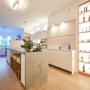 ハンブルクの大きいモダンスタイルのおしゃれなキッチン (一体型シンク、フラットパネル扉のキャビネット、白いキャビネット、コンクリートカウンター、ベージュキッチンパネル、木材のキッチンパネル、白い調理設備、無垢フローリング、茶色い床、グレーのキッチンカウンター) の写真
