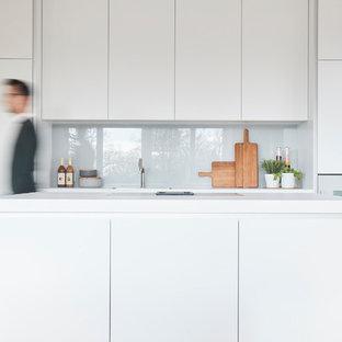 Moderne Küche mit flächenbündigen Schrankfronten, weißen Schränken, Quarzwerkstein-Arbeitsplatte, Küchenrückwand in Grau, Glasrückwand, weißen Elektrogeräten, hellem Holzboden, Kücheninsel, weißer Arbeitsplatte, Unterbauwaschbecken und beigem Boden in Hamburg