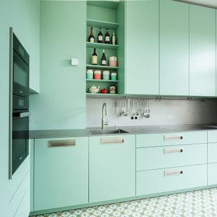 Cette photo montre une petite cuisine tendance en L fermée avec un évier intégré, un placard à porte plane, des portes de placard turquoises, un plan de travail en inox, une crédence grise, une crédence en dalle métallique, un électroménager noir, un sol turquoise et un plan de travail gris.