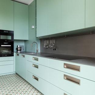 Aménagement d'une cuisine ouverte contemporaine en L de taille moyenne avec un placard à porte plane, des portes de placard turquoises, un plan de travail en inox, une crédence grise, une crédence en dalle métallique, un électroménager noir et un plan de travail gris.