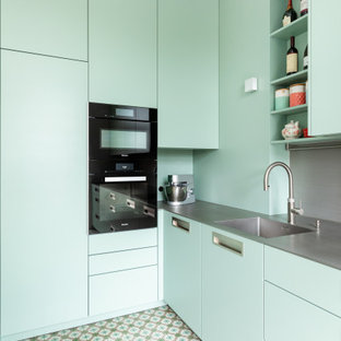 This is an example of a small contemporary l-shaped separate kitchen in Frankfurt with an integrated sink, flat-panel cabinets, green cabinets, stainless steel benchtops, grey splashback, metal splashback, black appliances, turquoise floor, grey benchtop and no island.