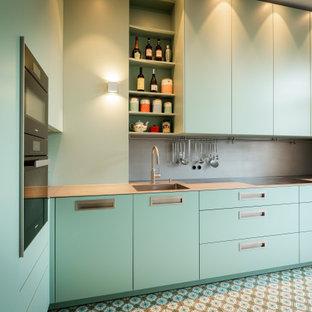 フランクフルトの小さいコンテンポラリースタイルのおしゃれなキッチン (一体型シンク、フラットパネル扉のキャビネット、ターコイズのキャビネット、ステンレスカウンター、グレーのキッチンパネル、メタルタイルのキッチンパネル、黒い調理設備、ターコイズの床、グレーのキッチンカウンター、アイランドなし) の写真