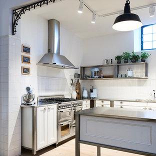 Offene, Mittelgroße Industrial Küche in L-Form mit Granit-Arbeitsplatte, Küchenrückwand in Grau, zwei Kücheninseln, Einbauwaschbecken, Schrankfronten mit vertiefter Füllung, weißen Schränken, Küchengeräten aus Edelstahl, braunem Holzboden und braunem Boden in Hamburg