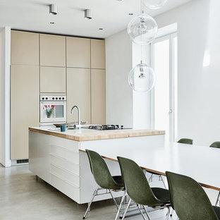 Ispirazione per una cucina abitabile minimalista di medie dimensioni con ante lisce, ante beige, top in legno, pavimento in cemento, isola, lavello da incasso e elettrodomestici in acciaio inossidabile