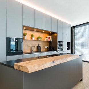Zweizeilige, Kleine, Offene Moderne Küche mit grauen Schränken, Rückwand aus Holz, schwarzen Elektrogeräten, braunem Boden, schwarzer Arbeitsplatte, Unterbauwaschbecken, flächenbündigen Schrankfronten, Granit-Arbeitsplatte, Küchenrückwand in Braun, braunem Holzboden und Kücheninsel in München