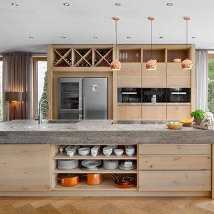Zweizeilige, Mittelgroße Moderne Wohnküche mit integriertem Waschbecken, flächenbündigen Schrankfronten, hellen Holzschränken, hellem Holzboden, Kücheninsel, beigem Boden, Arbeitsplatte aus Holz und schwarzen Elektrogeräten in Stuttgart