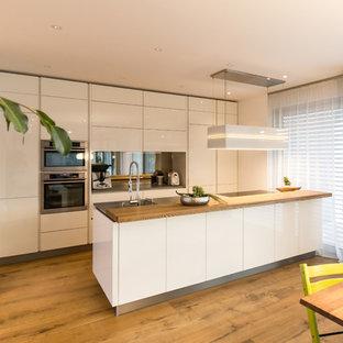 Offene, Zweizeilige, Mittelgroße Moderne Küche mit Einbauwaschbecken, flächenbündigen Schrankfronten, weißen Schränken, Küchenrückwand in Metallic, Rückwand aus Spiegelfliesen, Küchengeräten aus Edelstahl, braunem Holzboden, zwei Kücheninseln und braunem Boden in Stuttgart