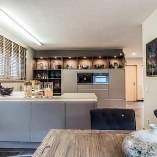 Offene, Mittelgroße Moderne Küche in U-Form mit Halbinsel, beiger Arbeitsplatte, braunem Boden, Einbauwaschbecken, flächenbündigen Schrankfronten, braunen Schränken und schwarzen Elektrogeräten in Sonstige