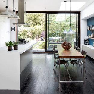 Mittelgroße Moderne Wohnküche mit dunklem Holzboden, braunem Boden, flächenbündigen Schrankfronten, weißen Schränken, Küchengeräten aus Edelstahl, Kücheninsel und weißer Arbeitsplatte in Hamburg