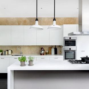 Mittelgroße, Zweizeilige Moderne Küche mit dunklem Holzboden, flächenbündigen Schrankfronten, weißen Schränken, Küchenrückwand in Beige, Küchengeräten aus Edelstahl, Kücheninsel, weißer Arbeitsplatte, Doppelwaschbecken und schwarzem Boden in Hamburg