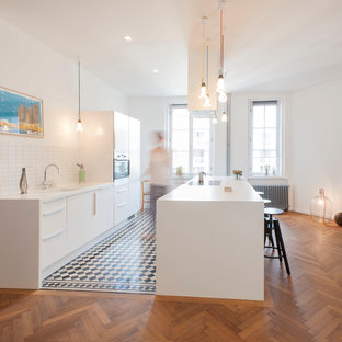 Design ideas for a large contemporary single-wall eat-in kitchen in Munich with flat-panel cabinets, white cabinets, white splashback, medium hardwood floors, an island, an undermount sink, ceramic splashback and panelled appliances.