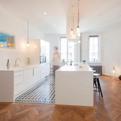 Large trendy single-wall medium tone wood floor eat-in kitchen photo in Munich with flat-panel cabinets, white cabinets, white backsplash, an island, an undermount sink, ceramic backsplash and paneled appliances