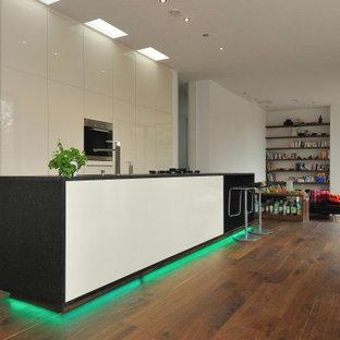 Zweizeilige, Große Moderne Wohnküche mit Unterbauwaschbecken, flächenbündigen Schrankfronten, beigen Schränken, Elektrogeräten mit Frontblende, braunem Holzboden, Kücheninsel, braunem Boden und schwarzer Arbeitsplatte in Stuttgart
