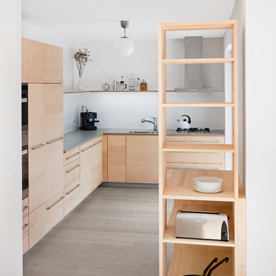 Example of a mid-sized trendy l-shaped light wood floor and beige floor open concept kitchen design in Stuttgart with flat-panel cabinets, light wood cabinets, laminate countertops, gray countertops, white backsplash, paneled appliances, a drop-in sink and no island