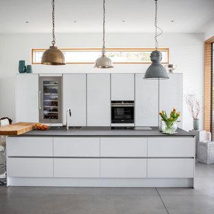 Zweizeilige Moderne Küche mit Unterbauwaschbecken, flächenbündigen Schrankfronten, weißen Schränken, schwarzen Elektrogeräten, Betonboden, Kücheninsel, grauem Boden und schwarzer Arbeitsplatte in Frankfurt am Main