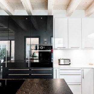 Mittelgroße Moderne Küche in L-Form mit flächenbündigen Schrankfronten, weißen Schränken, Küchenrückwand in Weiß, schwarzen Elektrogeräten, Kücheninsel und weißer Arbeitsplatte in München