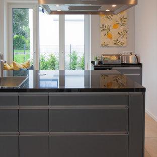 Foto di una grande cucina moderna con lavello da incasso, ante lisce, ante grigie, top in legno, elettrodomestici in acciaio inossidabile, pavimento in cementine, penisola, pavimento beige e top nero