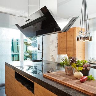 Пример оригинального дизайна: параллельная кухня-гостиная среднего размера в современном стиле с накладной раковиной, плоскими фасадами, светлыми деревянными фасадами, гранитной столешницей, черной техникой, полом из сланца, островом, черным полом и черной столешницей